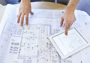 Shot of an architects hands examining blueprints and using a digital tablet